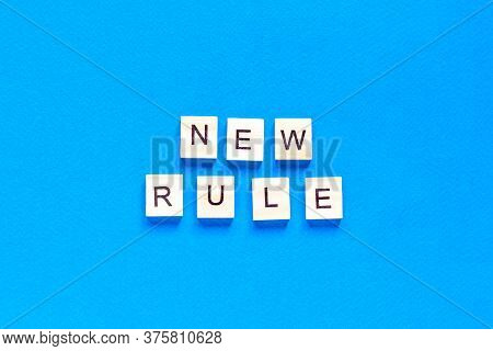 The New Rule Is Written In Wooden Letters On A Blue Background. New Concept. Business, Law, Rules, U
