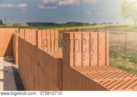 Construction Of A Small Family House. House Construction Site. Brick Wall On A Construction Site. A