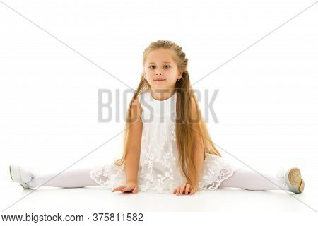 Little Girl Schoolgirl, Performs Gymnastic Twine In The Studio On A White Background. Concept Of Fit