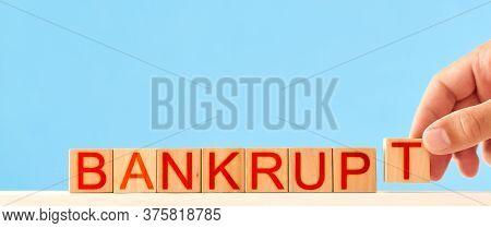 Bankrupt Concept. Man Stacks Wooden Blocks With The Inscription Bankrupt