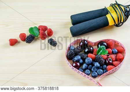 Group Of Various Berries, Dosing Tape And Jump Rope On The Light Background. Symbols Of Healthy Life
