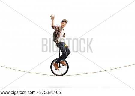 Young male student riding a unicycle on a rope and waving isolated on white background