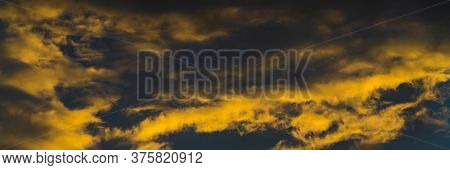 Panorama Golden Fluffy Clouds Illuminated By Disappearing Rays At Sunset And Dark Cumulonimbus Float