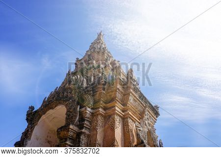 Look Up View Of Traditional And Ancient Thai Lanna Art Entrance Gate Of Under Bright Blue Sky With S