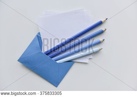 Selective Focus, Four Blue Pencils And White Papers Out Of The Blue Envelope