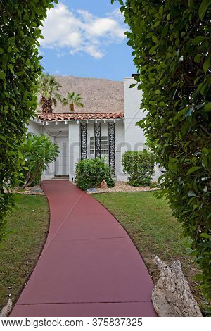 Path through hedge leading to bungalow