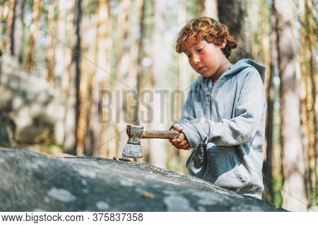 Tween Boy In Casual Outfit Cuts Stick With Axe On Rock In Forest