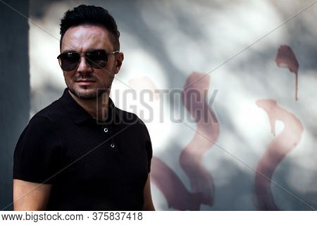 Stylish Guy With Glasses Looks Aside Against The Background Of A Spotted Fence. Strong And Strict Ma