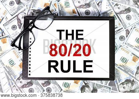The 80/20 Rule Text On White Paper On A Table Against The Backdrop Of Money And Glasses. Business Co