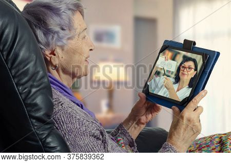 Telemedicine Female General Practitioner (gp) Explains To A Geriatric Patient The Importance Of Dete