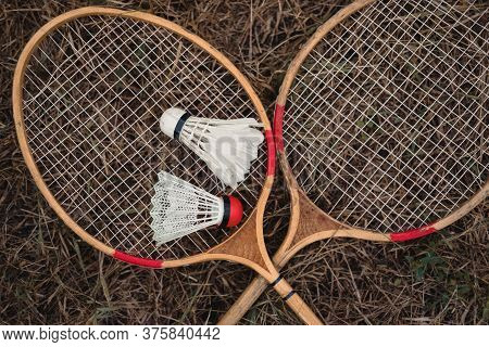 Wooden Badminton Rackets And A White Feather Shuttlecock And A Plastic One With A Red Head. The Game