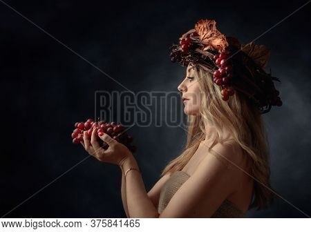 Portrait Of  Beautiful Caucasian Blonde Woman With Grapes. Shy Image Of A Blonde Nymph In A Wreath O