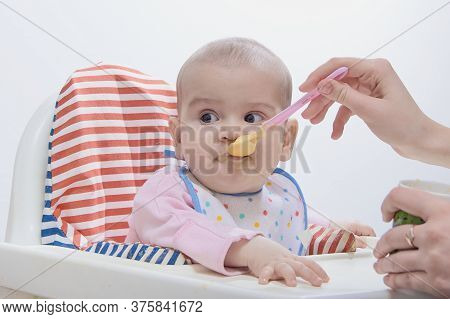 Feeding The Baby With A Spoon. A Mother Gives Healthy Food To Her Child At Home
