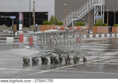 Empty Grocery Basket From The Supermarket And Its Reflection In The Rain In The Parking Lot