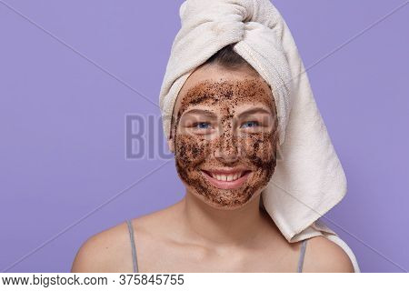 Shot Of Young Smiling Woman Applying Brown Cosmetic Mask On Her Face, Cleansing Her Skin At Home, Us