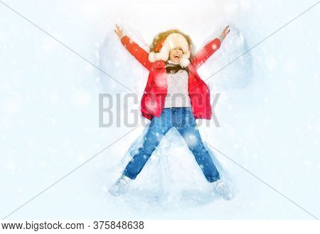 Snow Angel Concept With Happy Woman Enjoying First Snow, Lying In Snow And Making Snow Angel. Winter