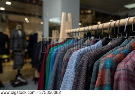 Expensive Mens Clothing Store. A Row Of Jackets On Hangers. Shoping Sale Background Theme. Clothes O