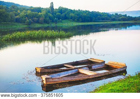 Old Sunken Wooden Boat . River Shore With Fishing Boats