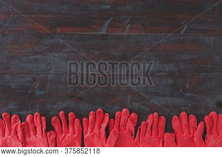 Line Of Red Housekeeping Construction Gloves On A Dark Wooden Background, Place For Text, Concept Of