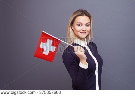 Immigration And The Study Of Foreign Languages, Concept. A Young Smiling Woman With A Switzerland Fl