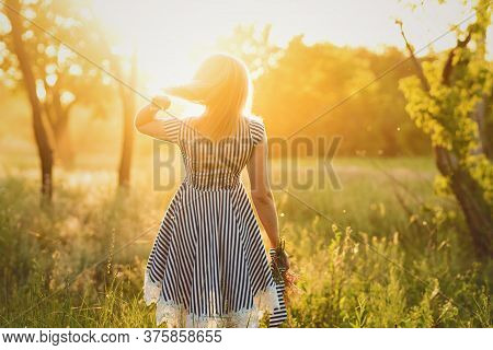 Unrecognizable Woman In Striped Sundress Holds Bouquet Wildflowers In Hand On Background Of Green Fi