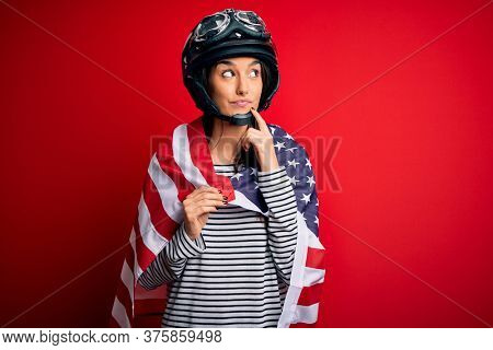 Young beautiful patriotic motorcyclist woman wearing moto helmet and united states flag serious face thinking about question, very confused idea