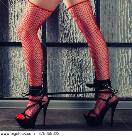 Bdsm Outfit For Adult Sex Games. Women's Legs In Red Fishnet Stockings And High Heels Are Shackled W