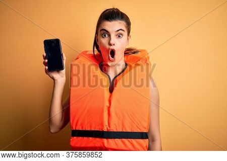 Young beautiful brunette woman wearing safe lifejacket showing smartphone scared in shock with a surprise face, afraid and excited with fear expression
