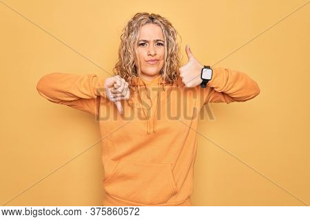 Young beautiful blonde sporty woman wearing casual sweatshirt over yellow background Doing thumbs up and down, disagreement and agreement expression. Crazy conflict