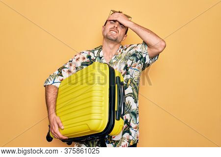 Handsome tourist man with blue eyes on vacation holding suitcase over yellow background stressed and frustrated with hand on head, surprised and angry face