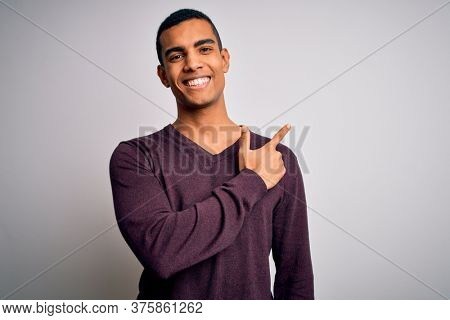 Young handsome african american man wearing casual sweater over white background cheerful with a smile of face pointing with hand and finger up to the side with happy and natural expression on face