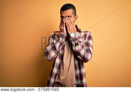 Young handsome african american man wearing casual shirt standing over yellow background rubbing eyes for fatigue and headache, sleepy and tired expression. Vision problem