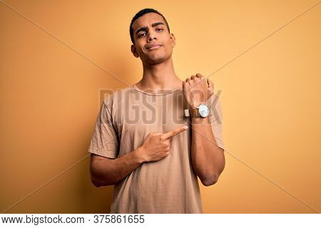 Young handsome african american man wearing casual t-shirt standing over yellow background In hurry pointing to watch time, impatience, looking at the camera with relaxed expression