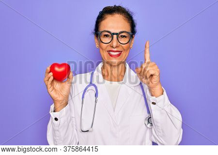 Middle age senior cardiologist doctor woman holding red heart over purple background surprised with an idea or question pointing finger with happy face, number one
