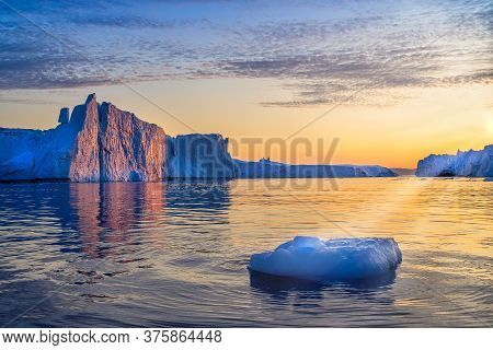 Greenland Ilulissat Glaciers At Ocean At Polar Night With Sun Rays