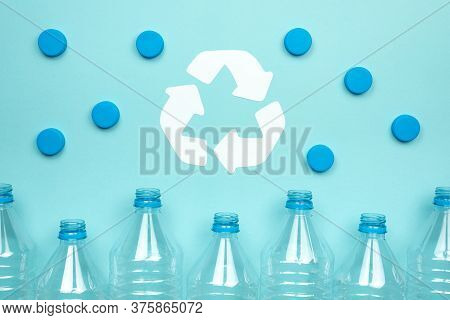 Horizontal Color Image With A Front View Of A Clear Plastic Bottles With Caps On A Blue Background.