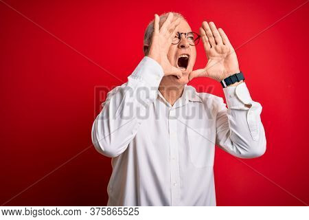Middle age handsome hoary man wearing casual shirt and glasses over red background Shouting angry out loud with hands over mouth