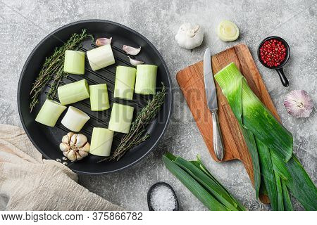 Raw Braised Leek Sultan On Grill Pan Uncooked With Herbs Ingredients  , On  Grey Textured Background