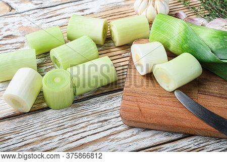 Green Chopped Leek Sultan On Choppong Board Over White Wood Table Side View.