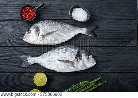 Raw Whole Pair  Dorado Or Sea Bream Fish With Herbs For Grill Uncooked  On Black Wooden Table Top Vi