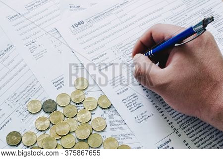 Us Tax Form 1040 With Hand Holding A Pen Near Golden Coins. Tax Forms Law Documents Usa. Business Ma