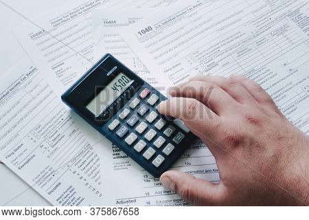 Us Tax Form 1040 With Hand Calculating On A Calculator. Tax Forms Law Documents. Usa Business Mathem