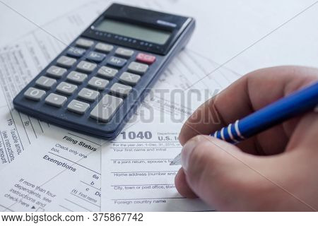 Us Tax Form 1040 With Hand Holding A Pen Nea A Blank Calculator. Tax Forms Law Documents. Usa Busine