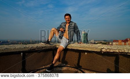 A Smart Guy In A Unbuttoned Shirt Sitting On A Parapet Of The Roof Of The Building At The Dawn Again