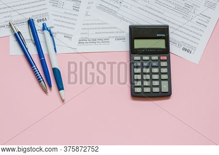 Us Tax Form 1040 With Calculator And Pen. Tax Form. Law Document Usa. Pink Background. Mathematics B