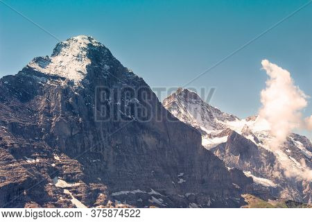 The Eiger North Face And Snow Capped Peak, In The Background The Top Of Jungfrau On A Bright Day In
