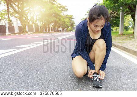 Young Woman Runner Tying Laces Her Shoelaces.  Asian Women Tying Her Black Shoe.  Woman Wear Running