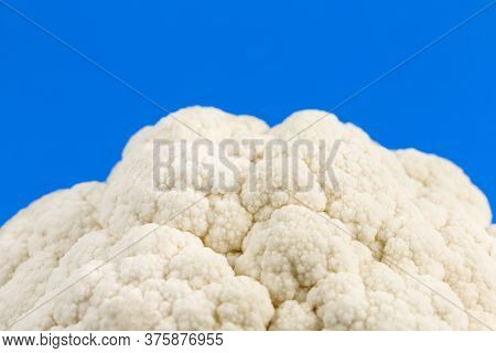 Close-up Of Delicious White Cauliflower Illustrating A Healthy Lifestyle Isolated On Blue Background