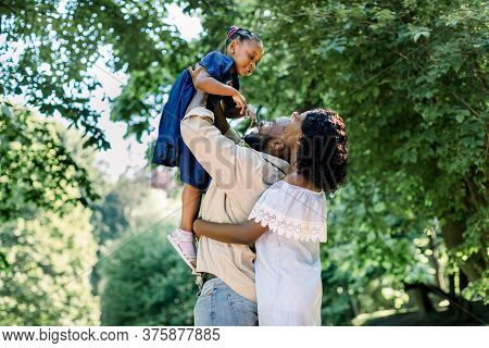 Summer Shot Of Happy African Family Playing In The Park. Family Portrait With Happy People Smiling A