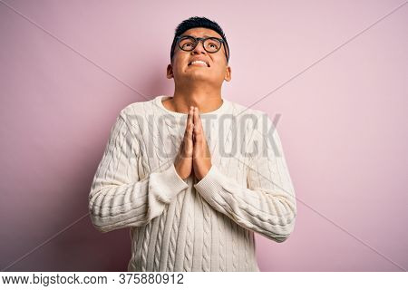 Young handsome latin man wearing white casual sweater and glasses over pink background begging and praying with hands together with hope expression on face very emotional and worried. Begging.